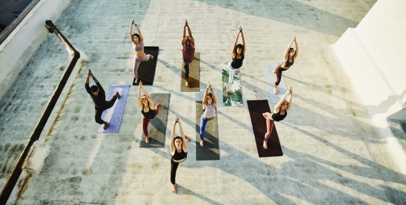 Overhead view of yoga class in warrior pose while practicing on rooftop